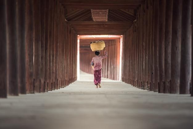 Birmese vrouw die bamboemand op hoofd zet