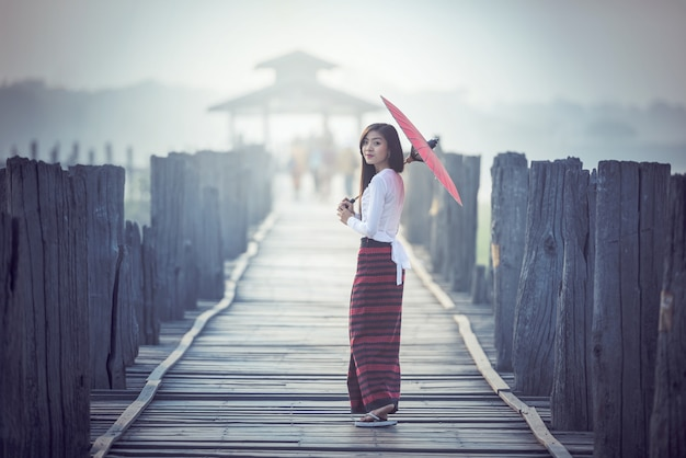 Birmese vrouw die traditionele rode paraplu en lopen op u bein bridge, myanmar