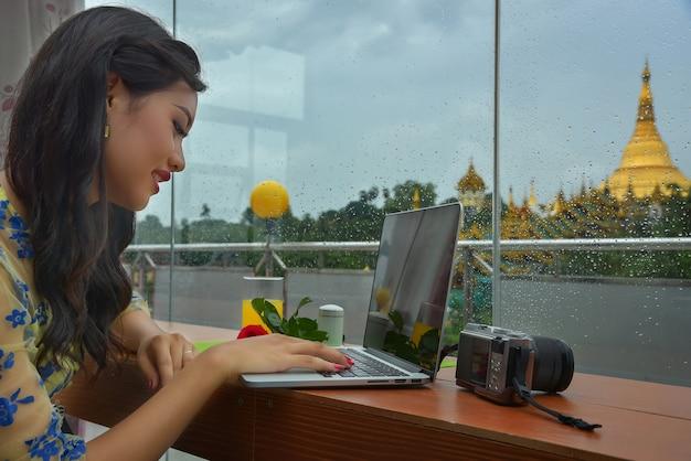 Birmese vrouwelijke toeristen zitten en ontspannen, spelen een notebook en een camera in de kamer met uitzicht op de prachtige shwedagon pagoda.