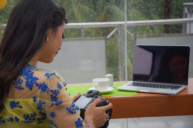 Birmese vrouwelijke toeristen zitten en ontspannen, spelen notebooks en bekijken foto's in de camera in hun handen.