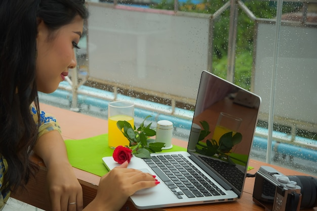 Birmese vrouwelijke toeristen zitten en ontspannen, spelen notebooks en zien foto's in de camera in de kamer met uitzicht op de prachtige shwedagon pagoda.