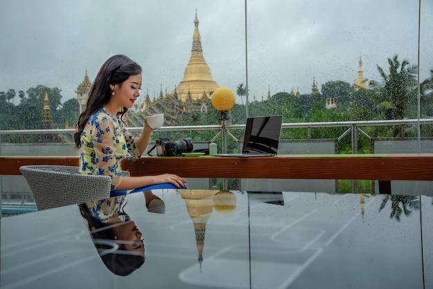 Birmese vrouwen, zittend in koffie en ontspannen, spelen een notebook met een camera in de kamer met uitzicht op de prachtige shwedagon pagoda.