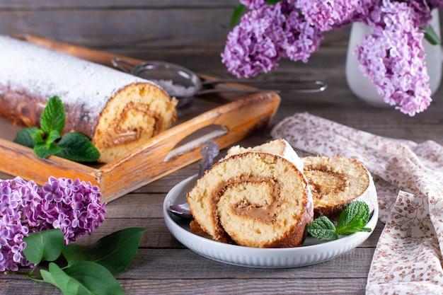 Biscuitbroodje met room in een plaat op een houten lijst