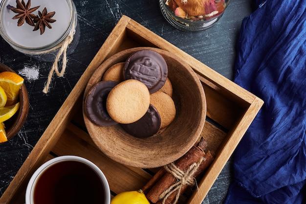 Biscuitkoekjes met chocolade en een kopje thee.