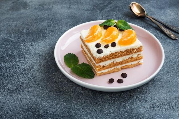 Biscuitlaagjes met botercrème, gedecoreerd met schijfjes mandarijnchocolade en munt. heerlijk zoet dessert voor thee.