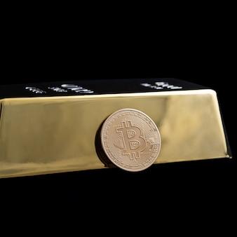 Bitcoin cryptocurrency en goudstaaf op een zwarte achtergrond.