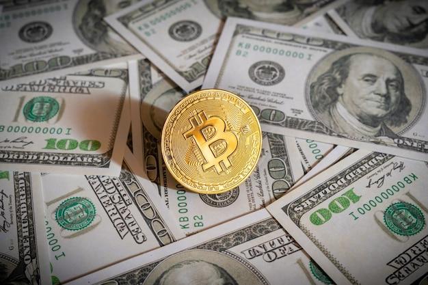 Bitcoin cryptocurrency munt en dollarbiljetten op de achtergrond