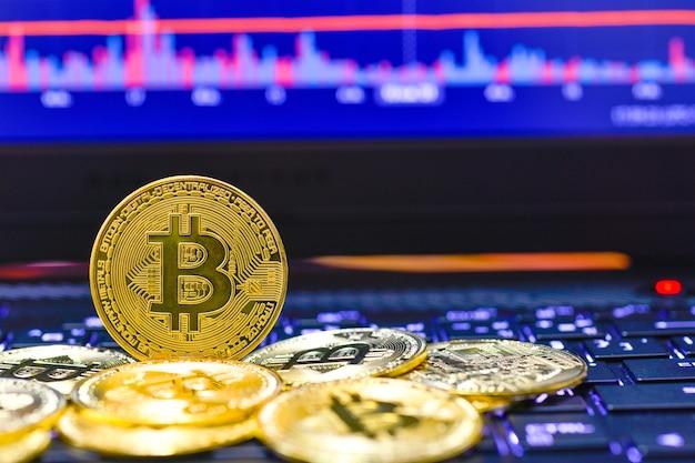 Bitcoin cryptocurrency-stapel op een achtergrond van groeigrafiek op een scherm van laptop