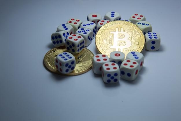Bitcoin cryptocurrency tokens in midden van dobbelstenen op donker witte achtergrond.