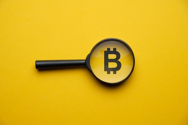 Bitcoin cryptocurrency zoekconcept met vergrootglas op een gele ruimte.