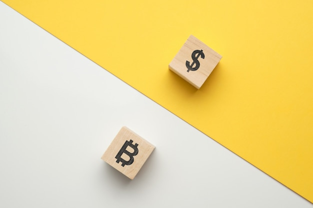 Bitcoin en dollar cryptocurrency confrontatieconcept met pictogrammen op houten blokken.