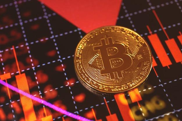 Bitcoin en rode voorraadgrafiek op de achtergrond, het conceptfoto van het cryptovalutafinanciën