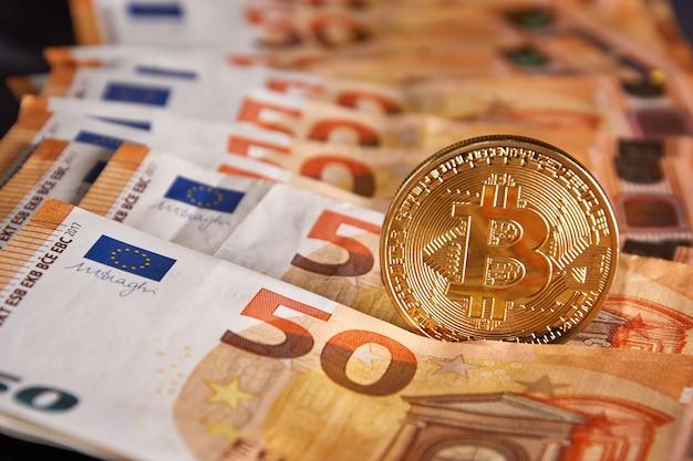 Bitcoin fysieke gouden munt op bankbiljetten van 50 eurobiljetten. bitcoin is een blockchain-cryptovaluta