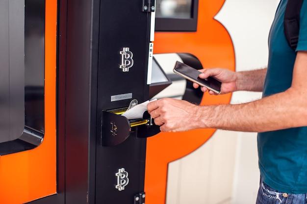 Bitcoin-geldautomaat. man die bitcoin-atm gebruikt om cryptomunten te kopen of te verkopen. controle en smartphone in handen houden. elektronische geldvaluta