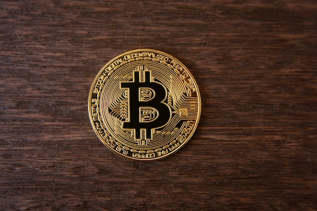 Bitcoin gouden munt op donker hout