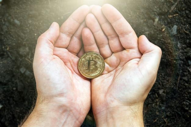 Bitcoin in de handen van de mijnwerker. gouden bitcoins delven