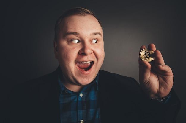 Bitcoin in dikke grappige man hand, digitall symbool van een nieuwe virtuele valuta
