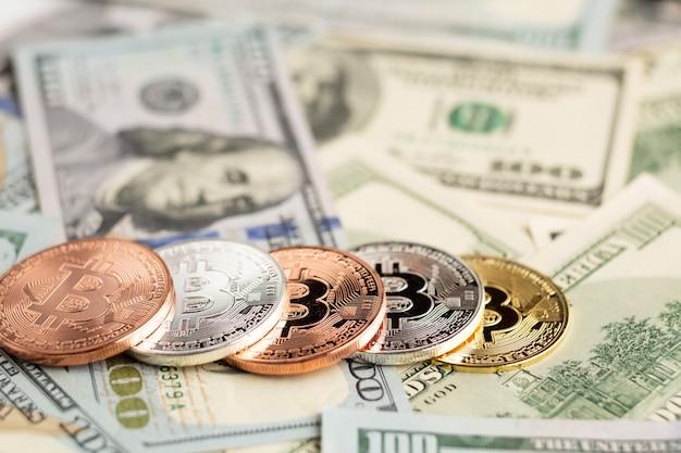 Bitcoin in verschillende kleuren bovenop dollarrekeningen