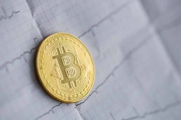 Bitcoin leeft. de gouden munt ligt op een papier