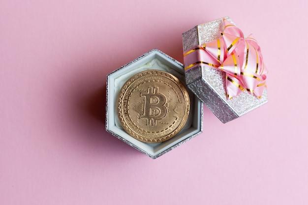 Bitcoin ligt in kleine geschenkverpakking op roze achtergrond.