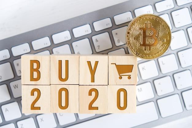 Bitcoin met getallen op houten kubussen op een wit toetsenbord