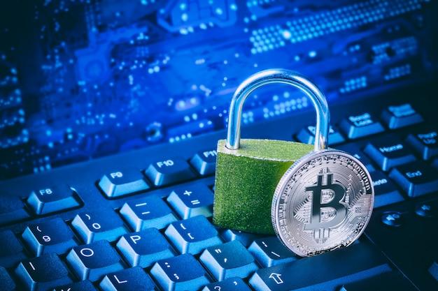 Bitcoin met hangslot op computermoederbord.