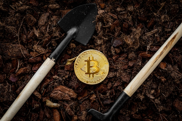 Bitcoin-mijnbouw. bitcoin besprenkeld met aarde, ernaast is een kleine schop