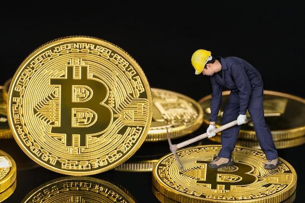 Bitcoin-mijnwerker met mattock die gouden bitcoin graaft op zwarte achtergrond