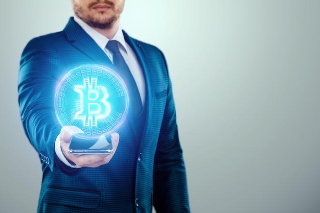 Bitcoin munt in de hand van een zakenman, hologram. digitale valuta, virtueel geld en cryptocurrency, blockchain-technologie.