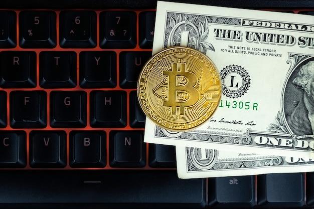 Bitcoin-munt met laptop en amerikaanse dollars. bitcoin gouden munten op een dollar bankbiljetten office achtergrond zwarte laptop mobiel.