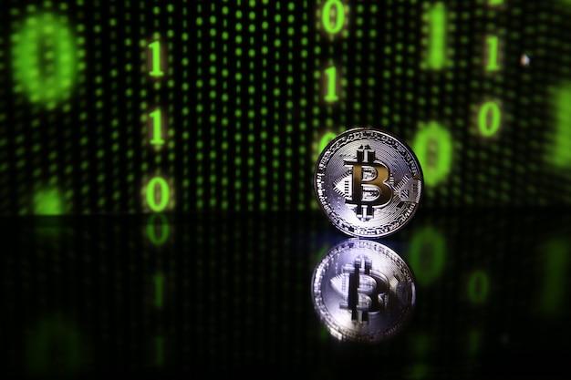 Bitcoin munt met reflectie op zwarte achtergrond met groene binaire code