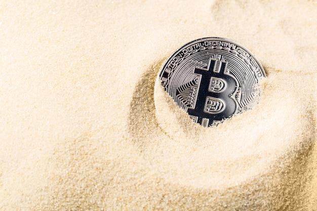Bitcoin munt zinken in het zand.