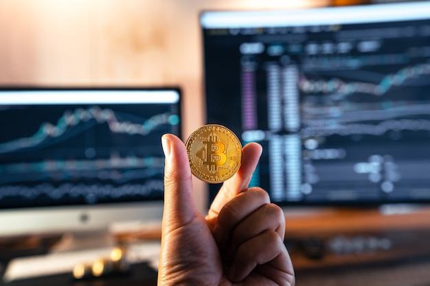 Bitcoin-munten in de hand voor de computer en bitcoin-grafiek
