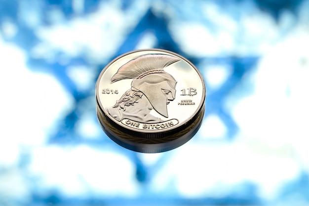 Bitcoin-munten over de israëlische vlag, het concept van virtueel geld, close-up.