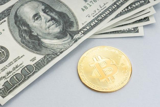 Bitcoin-muntstuk en een stapel amerikaanse dollarbankbiljetten. blockchain-geld versus fiat-geldconcept