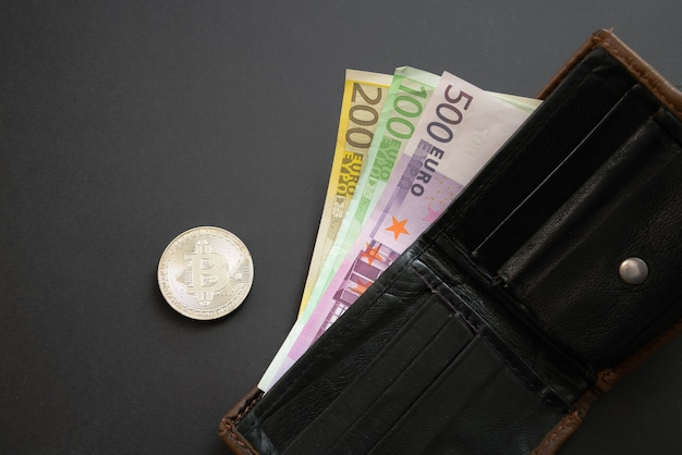 Bitcoin naast euro-bankbiljetten die uit een portemonnee op zwarte achtergrond steken. digitale valuta, blokketenmarkt. eurobiljetten naast cryptomunt