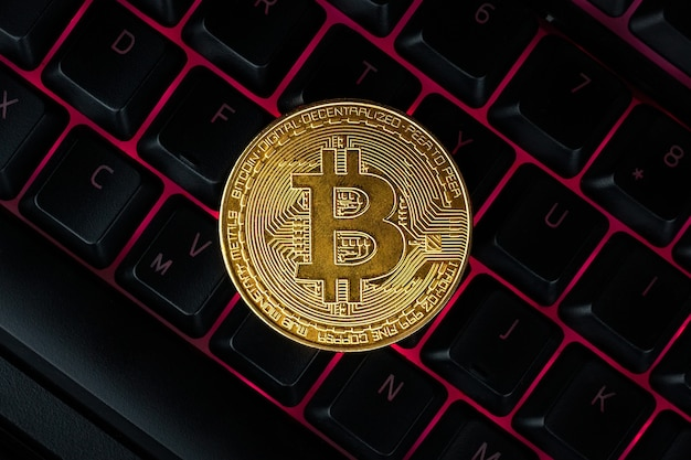 Bitcoin op computertoetsenbord op achtergrond, symbool van elektronisch virtueel geld en cryptocurrency-concept voor mijnbouw.