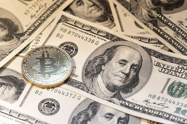 Bitcoin op de achtergrond van 100 dollarbiljetten.