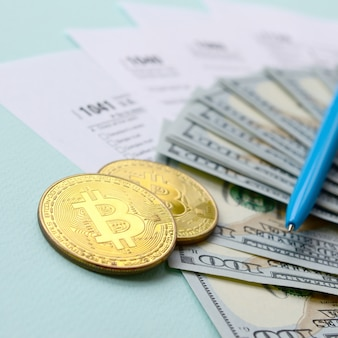 Bitcoins ligt met de belastingformulieren en honderd dollarbiljetten
