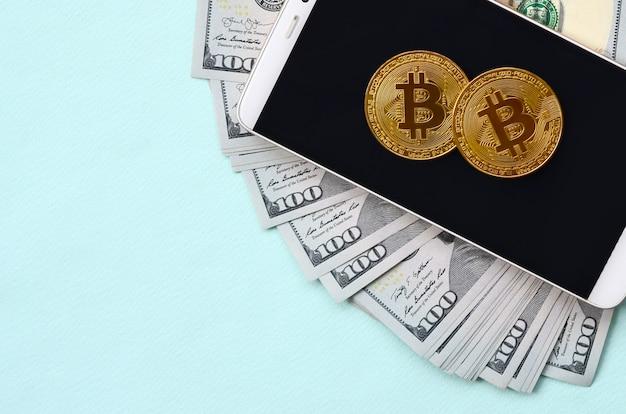 Bitcoins ligt op een smartphone en honderd dollarbiljetten op een lichtblauw