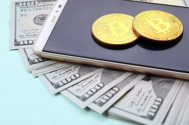 Bitcoins ligt op een smartphone en honderd dollarbiljetten op een lichtblauwe achtergrond
