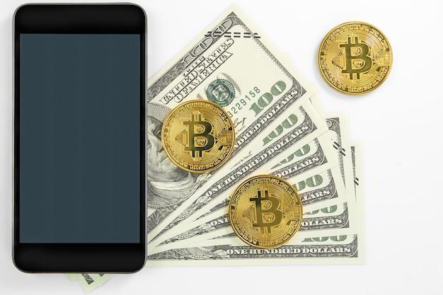 Bitcoins munt en amerikaanse bankbiljetten van honderd dollar met smartphone mock-up