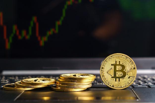 Bitcoins munt op toetsenbordcomputer. close up van bitcoin crypto valuta munten met trading exchange markt prijsgrafiek op de achtergrond