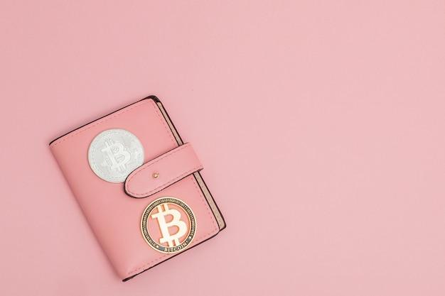 Bitcoins op een roze portefeuille op het roze met copyspace