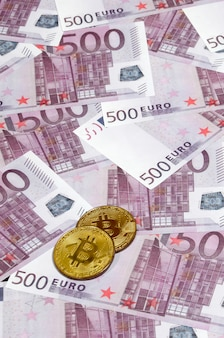 Bitcoins over stapel van vijfhonderd euro bankbiljetten.