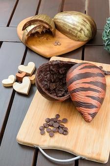 Bittere chocolade paasei met amandelkrokant, versierd met eetbare verf, op een houten bord. omringd door chocoladecallets, houten harten en chocolade-ei met karamelvulling.