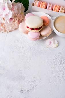 Bitterkoekjes en kopje koffie met bloemen over witte textuur