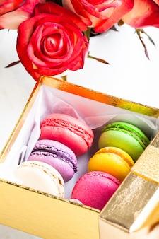 Bitterkoekjes in geschenkdoos en rozen in vaas