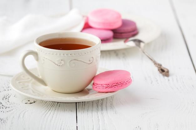 Bitterkoekjes met hete thee op houten tafel.