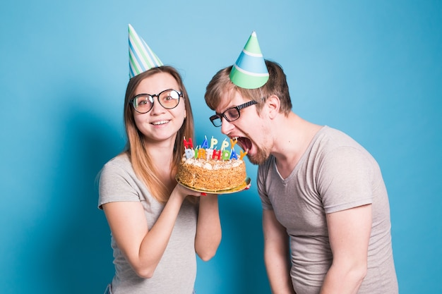 Bizar jong koppelmeisje en jongen met papieren hoeden willen een stuk felicitatietaart afbijten. verjaardag en gefeliciteerd concept.